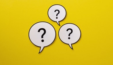 Three speech bubbles with question marks centered over a bright yellow background with copy space